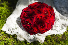 Round wedding bouquet of red or crimson roses on lace wedding dress. Round wedding bouquet of red or crimson roses on the train of lace wedding dress on green Royalty Free Stock Images