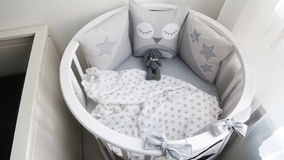 Round white baby bed with gray pillows stock video