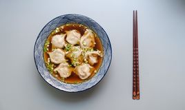Round White and Blue Ceramic Bowl With Cooked Ball Soup and Brown Wooden Chopsticks Stock Photography