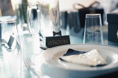 Round White Ceramic Plate Near Glass Cups and Groom Sign Royalty Free Stock Image