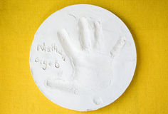 Round white clay dish with a small child's handprint. Stock Photo