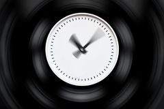 Round white clock with blurred arrows on a dark isolated background Stock Photo