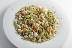 Round white dish of risotto with artichokes and seafood. Isolated on white background Royalty Free Stock Image