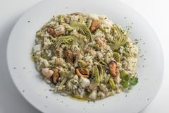 Round white dish of risotto with artichokes and seafood. Isolated on white background Stock Photo