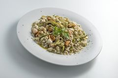 Round white dish of risotto with artichokes and seafood. Isolated on white background Royalty Free Stock Photos