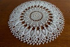 Round white handmade crochet lace doily on wood Royalty Free Stock Photo