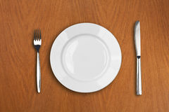 Round white plate, knife and fork on wooden table Stock Photography