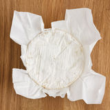 Round of white soft cheese with mould on wax paper Royalty Free Stock Photo