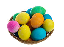 Round wicker basket of dyed eggs Stock Photo