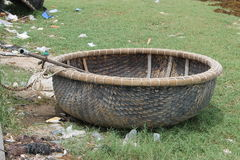 Round wicker boat standing on the grass. Round braided boat standing on the grass with a paddle Stock Image