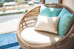 Round wicker wood chair with white cushion and comfort pillows. Near by the window and the common area of hotel royalty free stock photography