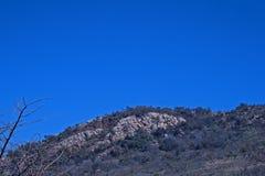 ROUND wierzchołek wzgórze PRZECIW niebieskiemu niebu Z ODSŁONIĘTĄ ROCKOWĄ warstwą fotografia stock
