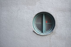 Round window. On a blank grey wall Stock Image
