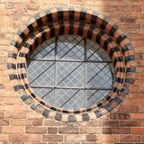 Round window with black brick. Rounded inset window with alternating red an black brick around harlequin patterned glass Royalty Free Stock Photos