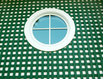 Round window on green. White framed round window with  green wooden strips Royalty Free Stock Images