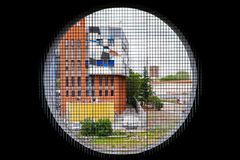 Round window overlooking the colorful buildings of the city stock photography
