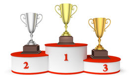 Round winners podium with trophy cups closeup. Sports winning and championship and competition success concept - golden, silver and bronze winners trophy cups on Royalty Free Stock Image