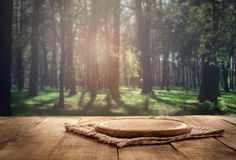 Round wood board on wooden table on forest background Stock Photo