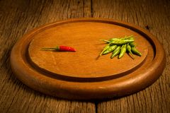 Round wood Chopping cutting board. chili peppers green and red royalty free stock photography