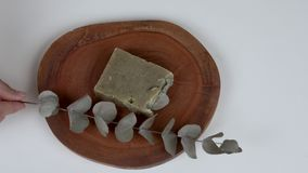 A round wooden board with a bar of lavender eucalyptus soap and a twig in front of it.