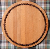 Round wooden board with circuit of the coffee beans. Free place for text. On plaid background. Round wooden cutboard with circuit of the coffee beans. Free space stock images