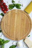 Round wooden board with spaghetti and different ingredients for cooking italian pasta on a white wooden background, flat lay. Top view. Copy space Royalty Free Stock Images