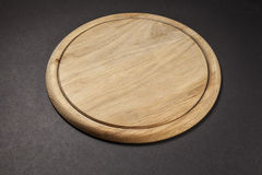 Round wooden breadboard  on grey Stock Photography
