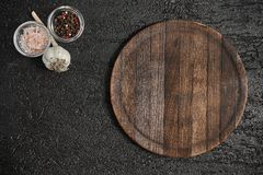 Round wooden cutting board on black table. Top view of empty kitchen trendy rustic wooden tray. royalty free stock photos