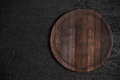 Round wooden cutting board on black table. Top view of empty kitchen trendy rustic wooden tray. Copy space for text. Food and menu background stock image