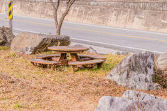 Round wooden picnic table at a roadside park Royalty Free Stock Image