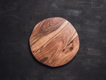 Round wooden tray. Or cutting board on black table. Top view of empty kitchen trendy rustic wooden tray saw cut imitation on black wooden background. Copy space stock photos