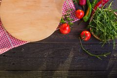 Round wooden tray or cutting board on black table. Top view of empty kitchen trendy rustic wooden tray saw cut imitation on black. Wooden background. Copy space royalty free stock photography