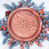 Round wooden tray surrounded with Christmas decorations on snow. Space for your text on the tray. Top view, square composition, toned image Stock Image