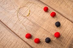 Round wool felt beads necklace handmade with red and black color beads on a wood table Stock Image