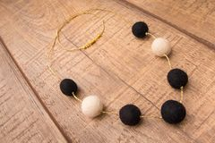 Round wool felt beads necklace handmade with white and black color beads on a wood table Stock Images