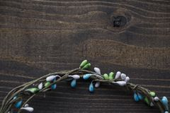 Round wreath with colourful beads at dark brown wooden background, flat lay, copy space royalty free stock photos