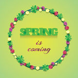 Round wreath with leaves, clovers and berries with lettering spring is coming inside it Stock Photos