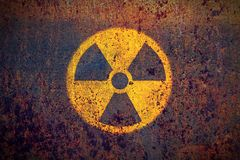 Round yellow and black radioactive ionizing radiation danger symbol. Painted on a massive rusty metal wall with dark rustic grunge texture background Stock Photography