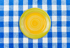 Round yellow plate on checked tablecloth. Round yellow plate on blue checked tablecloth Royalty Free Stock Photo