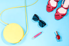 Round yellow purse, red nail polish, red lipstick, red sandals, sunglasses on a pastel blue background. Summer collection of female accessories Stock Photos