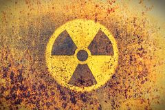 Round yellow radioactive ionizing radiation danger symbol painted on a massive rusty metal wall with rustic grunge texture stock photo