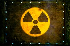Nuclear radioactive ionizing radiation nuclear danger warning symbol painted on massive rusty metal plate royalty free stock photos