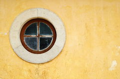Round yellow window. Round wood window with a stone frame on a old yellow wall Royalty Free Stock Photo
