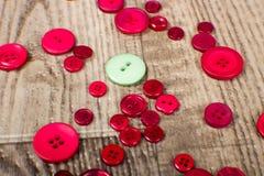 Round zieleń i czerwień barwiący guziki kłaść na drewnie groszkujemy tło Zdjęcia Stock