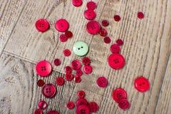 Round zieleń i czerwień barwiący guziki kłaść na drewnie groszkujemy tło Obrazy Royalty Free