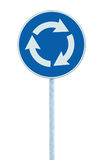 Roundabout crossroad road traffic sign isolated, blue, white arrows pointing left hand, large detailed closeup Stock Photos