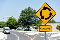 Roundabout sign at intersection. Truck leaving roundabout intersection with yellow cautionary sign Royalty Free Stock Image