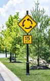 Roundabout Sign in New Upscale Industrial Park. Vertical shot of a roundabout traffic sign with speed limit sign below in an upscale industrial park.  Green Stock Photography