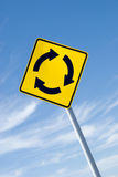 Roundabout Sign With Sky. Yellow roundabout traffic sign against blue sky Royalty Free Stock Photography