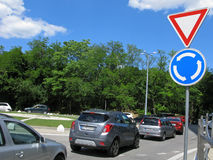 Roundabout traffic, road signs and cars on road Royalty Free Stock Photography